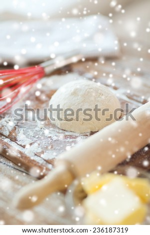 cooking, baking and home concept - close up of bread dough and utensils on cutting board - stock photo