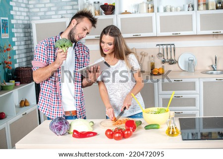 Cooking Broccoli for salad. Young and beautiful couple in love food cooking according to the recipe on the tablet while they are preparing breakfast in the kitchen.