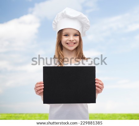 cooking, childhood, advertisement and people concept - smiling little chef girl, cook or baker with blank black paper over blue sky and grass background - stock photo