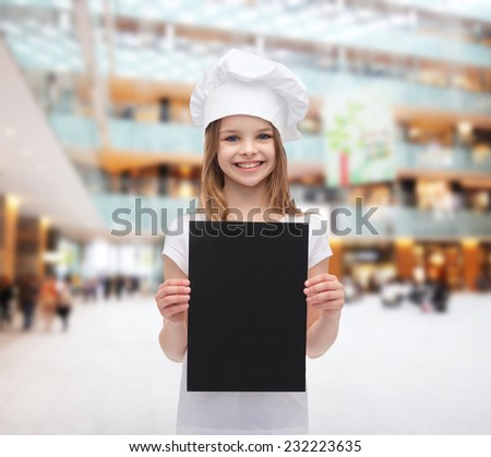 cooking, childhood, advertisement and people concept - smiling little chef girl, cook or baker with blank black paper over shopping center background - stock photo