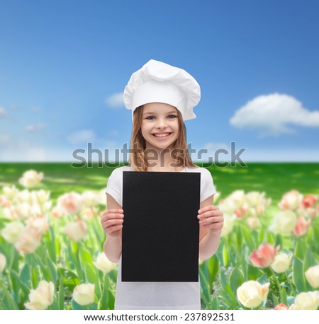 cooking, childhood, advertisement and people concept - smiling little chef girl, cook or baker with blank black paper over blue sky and field of flowers background - stock photo