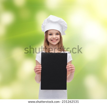 cooking, childhood, ecology, advertisement and people concept - smiling little chef girl or baker with blank black paper over green background - stock photo