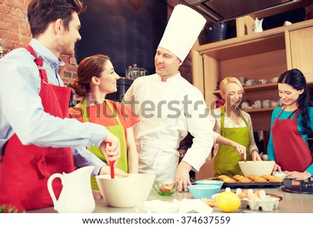cooking class, culinary, bakery, food and people concept - happy group of friends and male chef cook baking in kitchen - stock photo