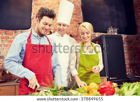 cooking class, culinary, food and people concept - happy couple and male chef cook cooking in kitchen - stock photo