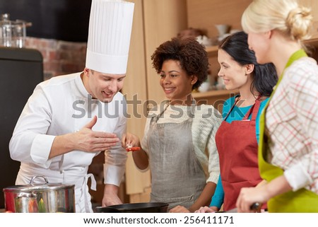 cooking class, culinary, food and people concept - happy group of women and male chef cook cooking in kitchen - stock photo