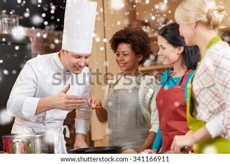 cooking class, culinary, food and people concept - happy group of women and male chef cook cooking in kitchen over snow effect - stock photo