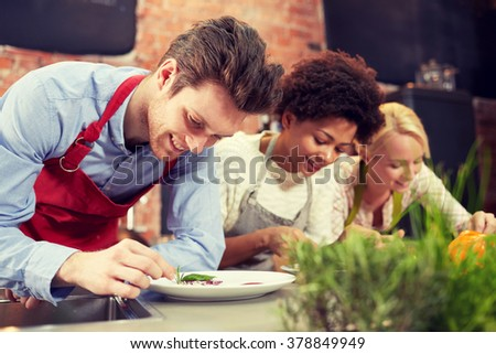 cooking class, friendship, food and people concept - happy women cooking and decorating plates with dishes in kitchen - stock photo