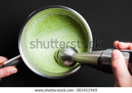 cooking, closeup whisking green smoothie inside a pan with blender on the black background - stock photo