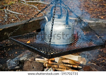 Cooking coffee in old time coffee pot over fire in the forest in fall. - stock photo