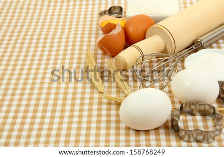 Cooking concept. Basic baking ingredients and kitchen tools on tablecloth background