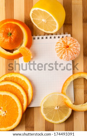 Cooking concept. Citrus with empty cookbook close up - stock photo