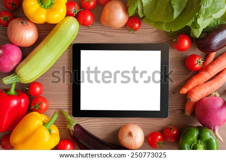 Cooking concept. Digital Recipe book. Tablet pc and ingredients for cooking vegetables over wooden background. Top view - stock photo