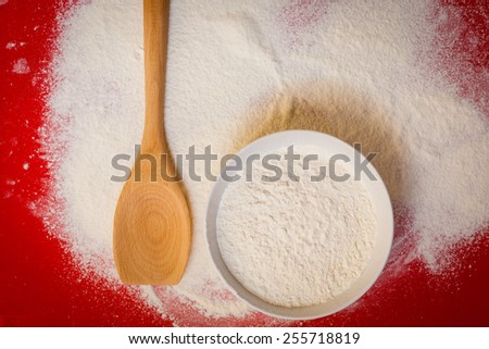 Cooking concept. Preparation for baking, bake ingredients to make a cake, wheat flour on red silicone mat, top view - stock photo
