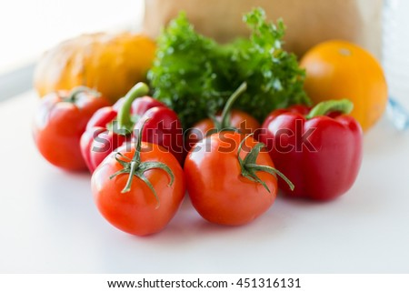 cooking, diet, vegetarian food and healthy eating concept - close up of fresh ripe juicy vegetables and greens on kitchen table at home - stock photo