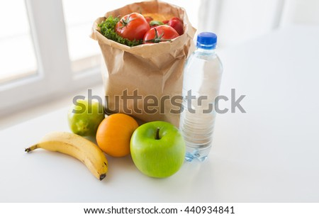 cooking, diet, vegetarian food and healthy eating concept - close up of paper bag with fresh ripe juicy fruits and vegetables and water bottle on kitchen table at home - stock photo
