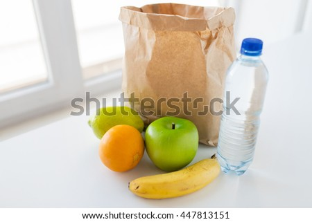 cooking, diet, vegetarian food and healthy eating concept - close up of paper bag with fresh ripe juicy fruits and water bottle on kitchen table at home - stock photo