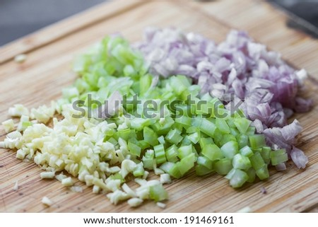 Cooking dinner, chopped vegetables onions, garlic, celery on desk - stock photo