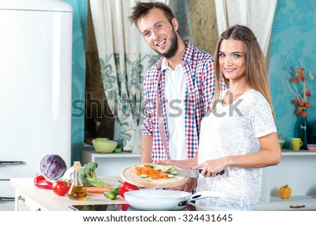 Cooking dinner together. Attractive loving couple is preparing to eat while standing in the kitchen. A girl holding a knife and throws vegetables in a frying pan