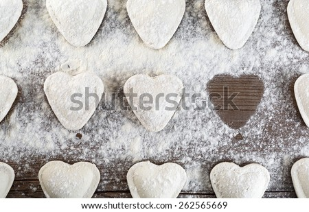 Cooking dumplings. Raw ravioli in the shape of hearts, sprinkle with flour, on wooden background closeup. Top view. - stock photo