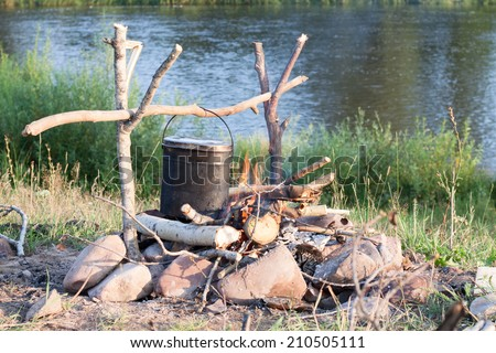 Cooking eat in bowler on the fire in a hike. Summer - stock photo