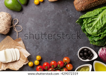 Cooking food ingredients. Lettuce salad, avocado, olives, cheese, bread and tomato cherry over stone background. Top view with copy space - stock photo