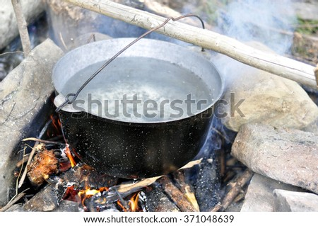 Cooking food with old tourist pot at outdoor fire place. Summer trekking activity.