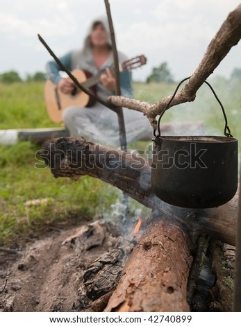 cooking fresh food in cauldron at camp on open fire - stock photo