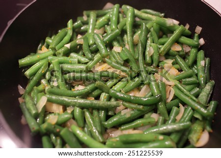 Cooking green beans with onions at home - stock photo