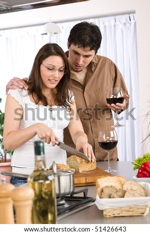 Cooking - happy couple together in modern kitchen drink red wine and cut bread