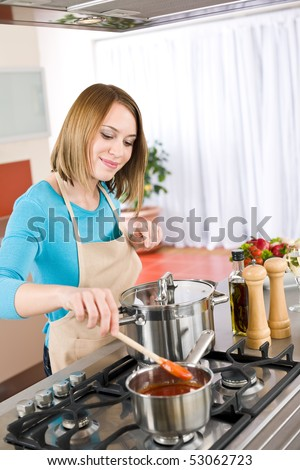 Cooking - Happy woman by stove in kitchen with pots and pans stirring tomato sauce - stock photo