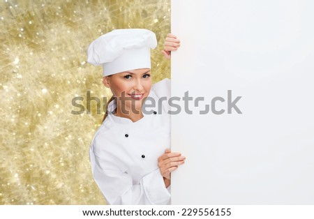cooking, holidays, advertisement and people concept - smiling female chef, cook or baker with white blank board over yellow lights background - stock photo