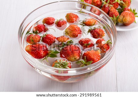 Cooking homemade strawberries jam: washed strawberries in water in a glass bowl. - stock photo