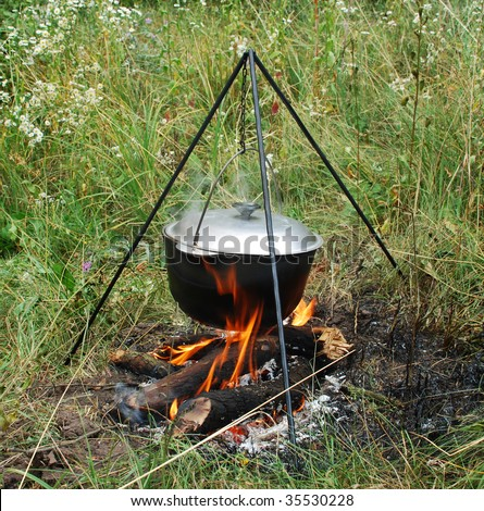 Cooking in a cauldron pot on a campfire - stock photo
