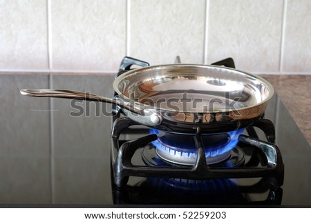 Cooking in a frying pan on a gas stove - stock photo