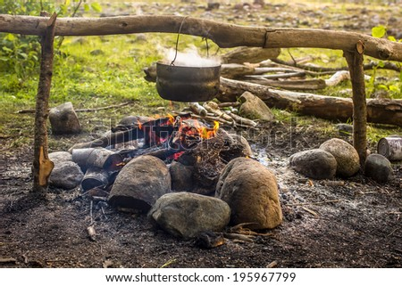 Cooking in a hike in the cauldron hanging over the fire, from the boiler coming white smoke - stock photo