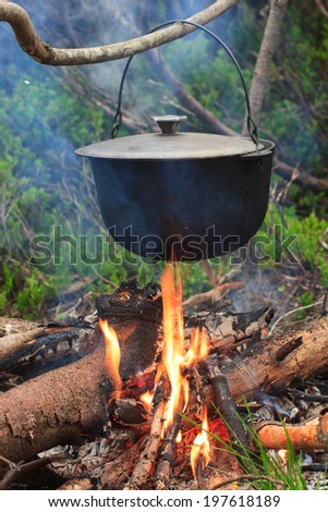 Cooking in field conditions, boiling pot at the campfire on picnic. - stock photo