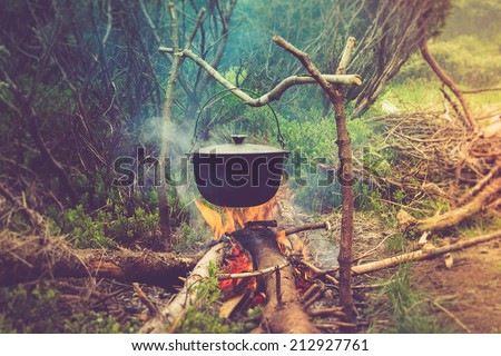 Cooking in field conditions, boiling pot at the campfire on picnic. Filtered image:cross processed vintage effect.  - stock photo