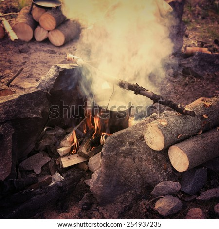 Cooking in field conditions, boiling pot at the campfire on picnic.Special toned photo in vintage style - stock photo