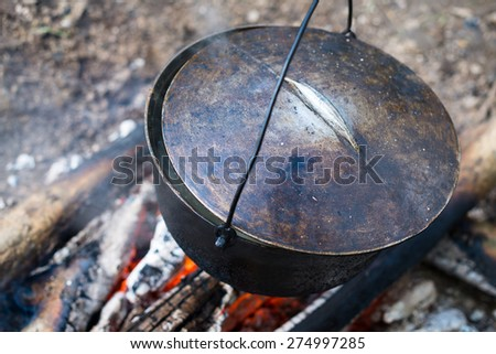 Cooking in the cauldron on the open fire. - stock photo
