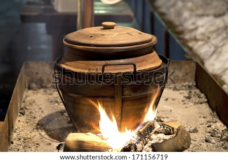 Cooking in the clay pot on fire - stock photo