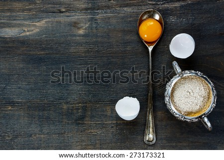 Cooking ingredients - egg yolk in vintage spoon and flour in vintage cup on wooden texture. Top view. - stock photo
