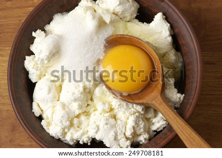 Cooking ingredients for cheesecakes: cottage cheese, sugar and yolk. - stock photo