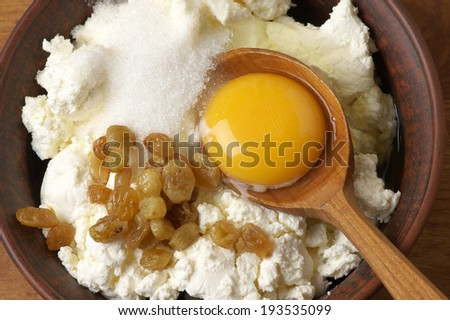 Cooking ingredients for cheesecakes: cottage cheese, sugar, raisin and yolk. - stock photo