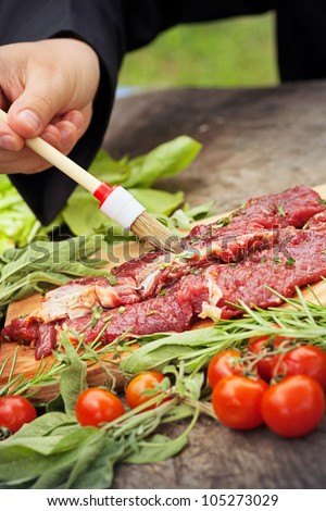 Cooking ingredients: marinated meat,oil,vinegar, herbs and vegetables. Chef is carving and marinating meat. - stock photo