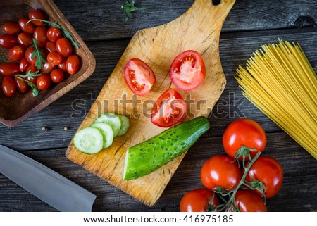 Cooking ingredients on wooden cutting board. Cut tomatoes, cucumber, fresh tomatoes on vine, cherry tomatoes, dry pasta, olive oil and arugula salad on rustic wooden backdrop. Top view food. - stock photo