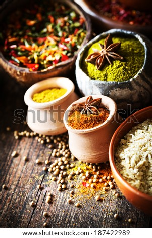 Cooking ingredients,spice/Asian cuisine with a low angle view of bowls of colourful spices on rustic wooden background - stock photo
