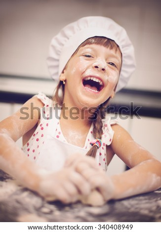 Cooking is fun. Little girl playing with flour  - stock photo