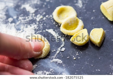 Cooking Italian pasta orecchiette, yellow dough, home kitchen - stock photo