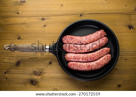 Cooking Italian sausage on a frying pan. - stock photo
