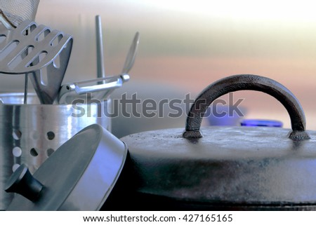 Cooking/kitchen concept. Cast iron and stainless steel kitchen utensils against steel background with reflections - stock photo